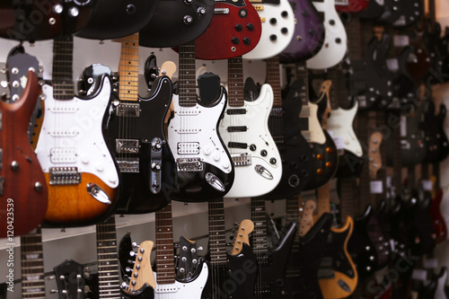 Deurstickers Muziekwinkel Guitars hanging on wall, closeup