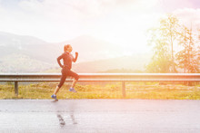 Young Sporty Woman Jogging On Road In Mountains