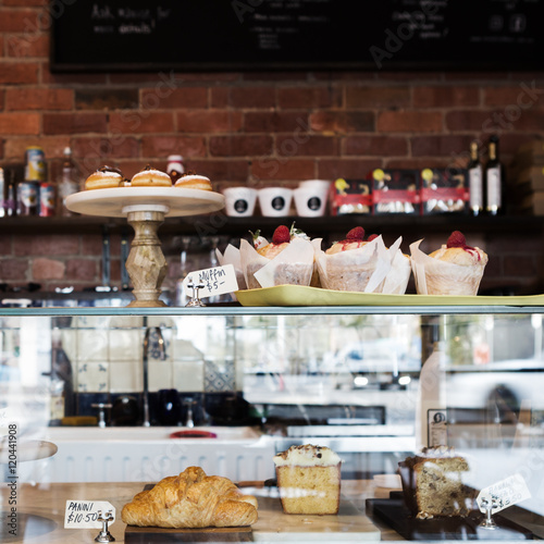 Foto op Plexiglas Bakkerij Cake display case in Melbourne cafe with rustic wall