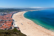 View over sandy beach coastline with ocean, sunlight, blue sky at Nazare, Portugal