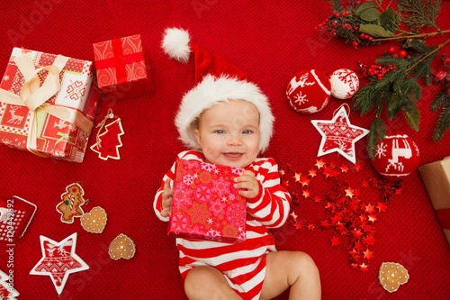Baby first christmas. Beautiful little baby celebrates Christmas. New  Year s holidays. Baby with santa hat with gift. Santa baby. 78a1c38ea991