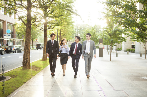 Young businessmen and women are walking the business district together