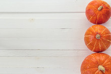 Background With Three Small Pumpkins On A White Wooden Boards. S