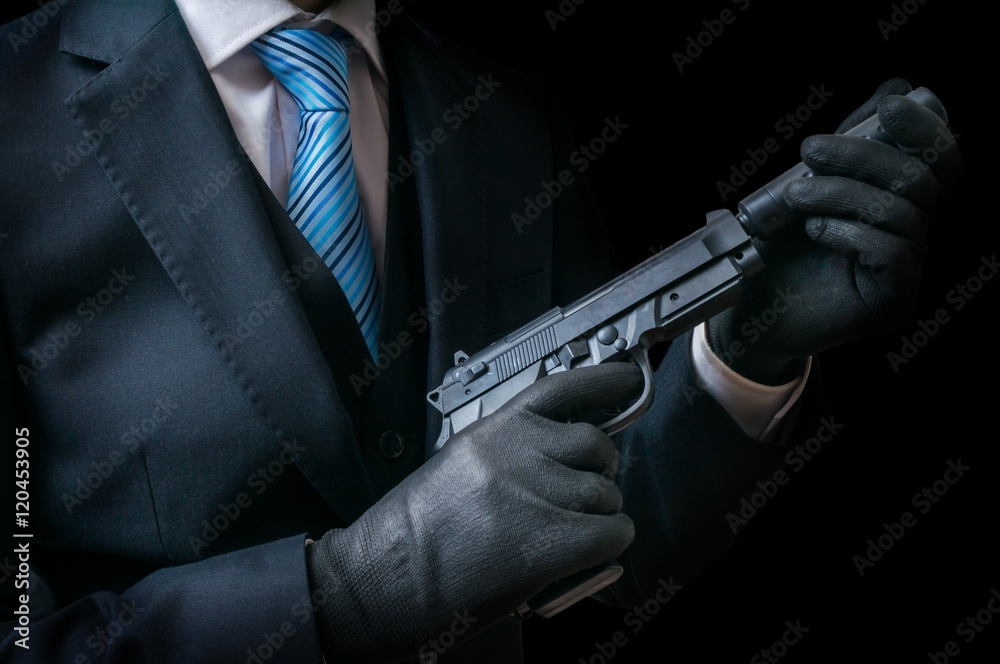 Fotografie, Obraz Mafia man or racketeer holds pistol with silincer in hands