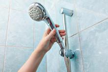 Close-up Of Human Hand Adjusts Holder Shower Head With Hose.