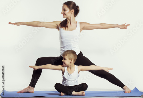 Staande foto School de yoga mother and son doing yoga (sports exercises), have fun and spend a good time together . isolated on white. the concept of a healthy lifestyle