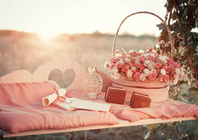 Little White Candle And Big Bouquet Of Roses Stand On The Bench