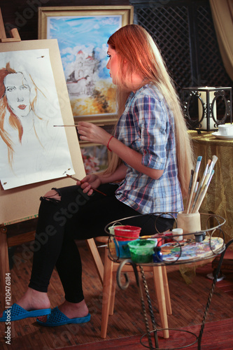 Keuken foto achterwand Koken Girl artist paints portrait of woman with pencil. Girl painter throw leg over other. Girl paints by pencil on easel. Pictures on background.