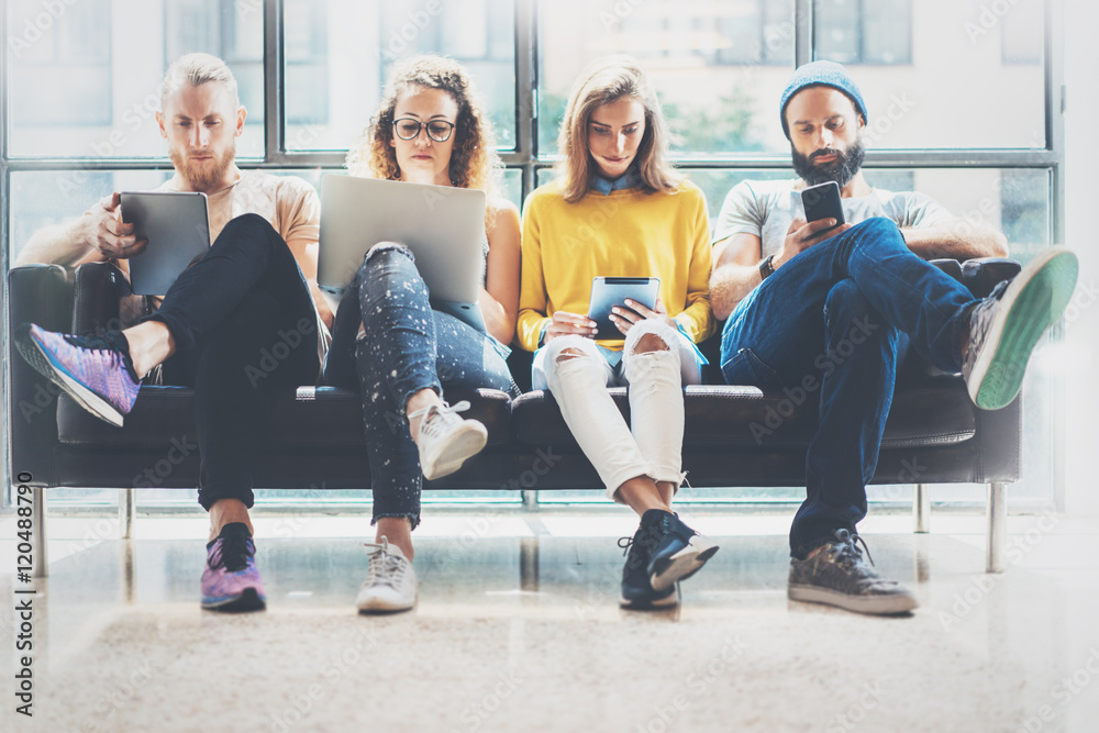 Fototapeta Group Adult Hipsters Friends Sitting Sofa Using Modern Gadgets.Business Startup Friendship Teamwork Concept.Creative People Working Together Marketing Project.Coworking Process Office Studio.Blurred.