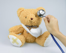 Brown Teddy Bear With Bandages And Broken Hand And Stethoscope Isolated On White Background