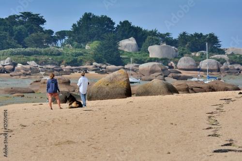 Photo  Deux femmes avec un chien de berger se promène au milieu des rochers à marée bas