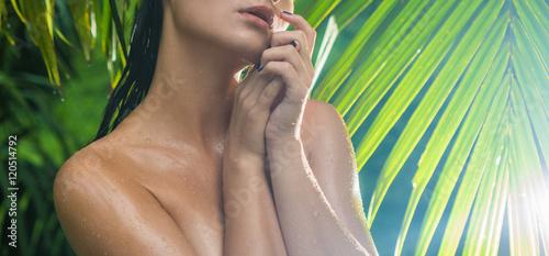 mloda-kobieta-w-dzungli-podczas-deszczowego-dnia-na-tle-palmowego-liscia