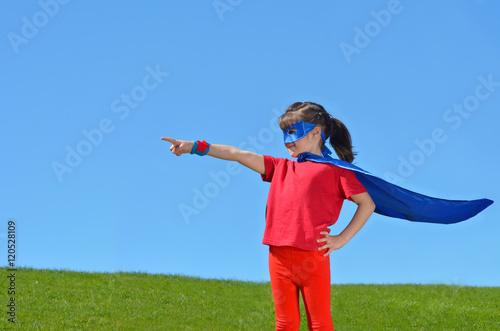 Photo  Superhero girl points towards dramatic blue sky