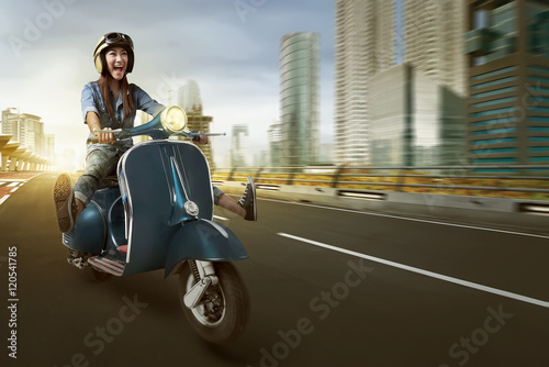 Asian woman riding scooter and wearing helmet Canvas Print