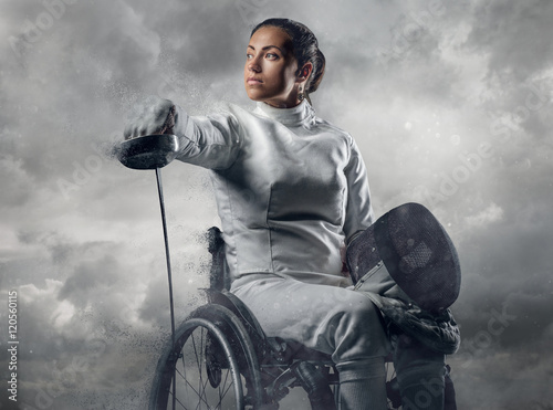 Valokuva  Female fencer in wheelchair with safety mask of a face holding r