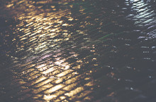 Wet Cobblestone During The Night Time After A Rain. It Reflects Some Light From The Grocery Store Window. Image Has A Vintage Effect Applied.