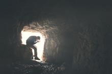 Sad Man Praying God In A Dark Cavern