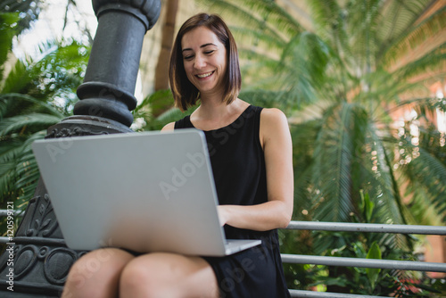Young brunette woman in black dress using laptop