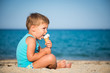 Sweet little boy eating ice cream on the beach, copy space