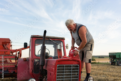 Senior farmer doing maintenance for tractor during harvest on countryside field