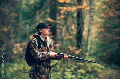 Fotografia Male hunter in the autumn forest. A man holding a gun.