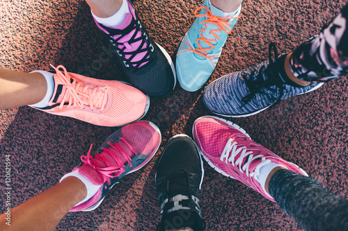 Fotografija  Closeup legs of athletes wearing sports shoes in a circle