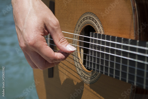 Fotografering  Male hand playing acoustic guitar