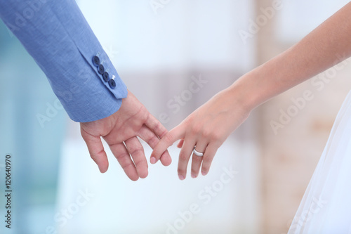 Fotografie, Obraz  Bride and groom holding hands together indoor