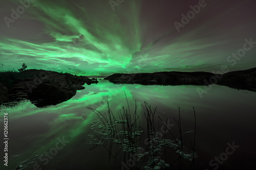 Fotografie, Obraz  Atmospheric glow of the aurora rays reflected in the perfectly smooth surface of