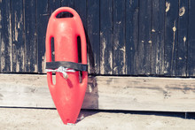 Close Up Of Red Lifeguard Rescue Can Equipment Against The Wooden Tower Wall At The Sandy Beach.