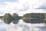 Piękny letni dzień nad jeziorem. Woda robi piękne odbicie. Obraz ma zastosowany efekt vintage. - 120689105