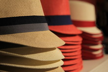 Straw Hats In Red And Black, Stacked Up For Sale In A Store In Shallow Focus.