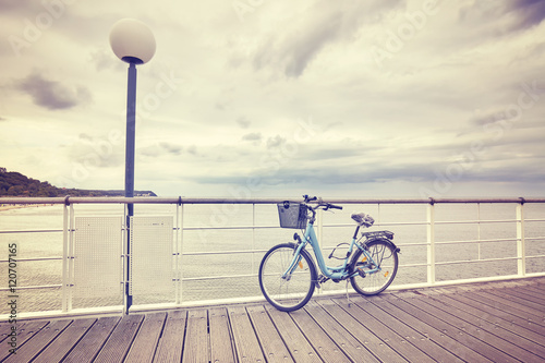 Deurstickers Fiets Vintage toned lonely bicycle with basket on empty pier, rainy summer day.