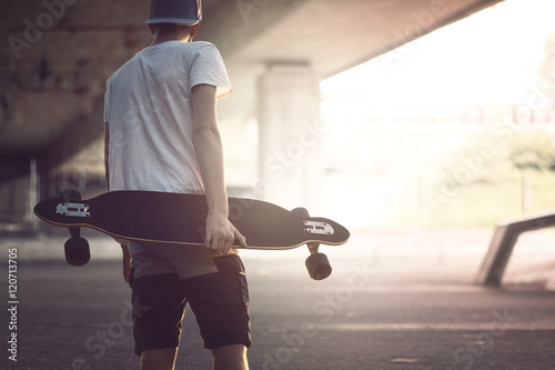 teenager with longboard in the city