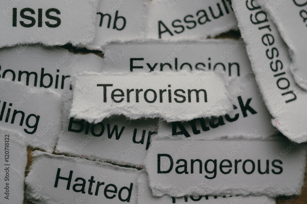 Fototapeta Torn paper with terrorism related words.