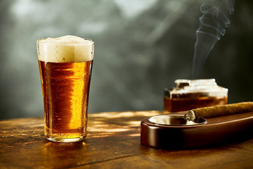 Single frothy beer with a burning cigar