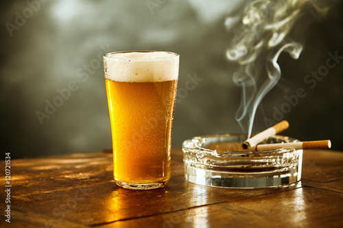Frothy ice cold beer and cigarette in a pub