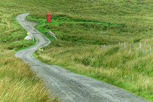 Lonely Red Phone Box Along A Serpentine Road In Scotland