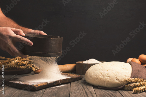 In de dag Bakkerij Baker sifts through the flour on a wooden table