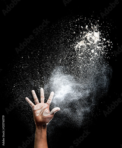 Fotografia Hand and flour on black background