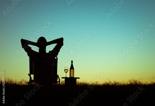 Poster Relaxation Woman relaxing watching the sunset and enjoying a glass of wine.