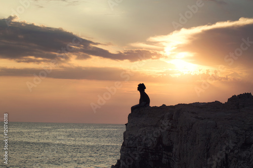Fotografia  mysterious boy sitting on the precipice of a cliff
