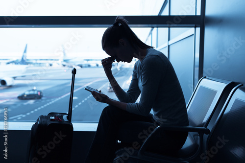 Obraz Stressed out female traveler at the airport.  - fototapety do salonu