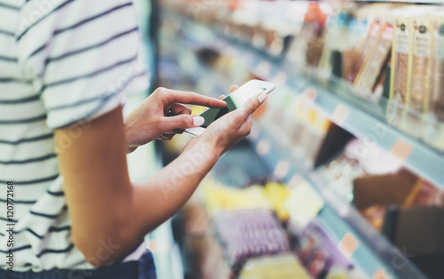 Fototapeta Woman shopping healthy food in supermarket background. Close up view girl buy products using digital gadget in store. Hipster at grocery using smartphone. Person comparing the price of produce obraz