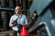 Senior male business owner mechanic holding power tool in repair garage