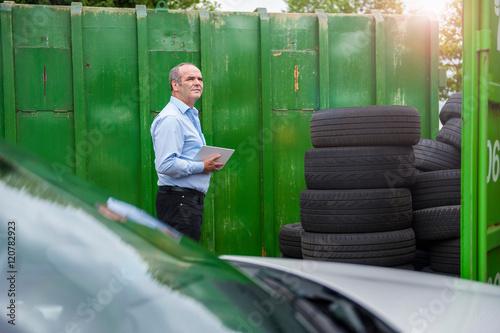 Senior male business owner monitoring stacked tyres in repair garage yard
