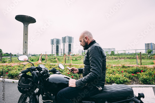 Mature male motorcyclist sitting on motorcycle reading smartphone text Poster