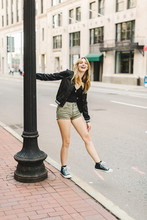 Young Woman Outdoors, Swinging On Lamp Post, Smiling