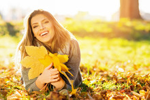 Beautiful Happy Young Woman In Park In Autumn Holding Leaves