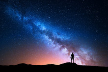 Milky Way. Beautiful Night Sky With Stars And Silhouette Of A Standing Alone Man On The Mountain. Milky Way With Red Light And Man On The Hill. Background With Galaxy And Silhouette Of A Man. Universe